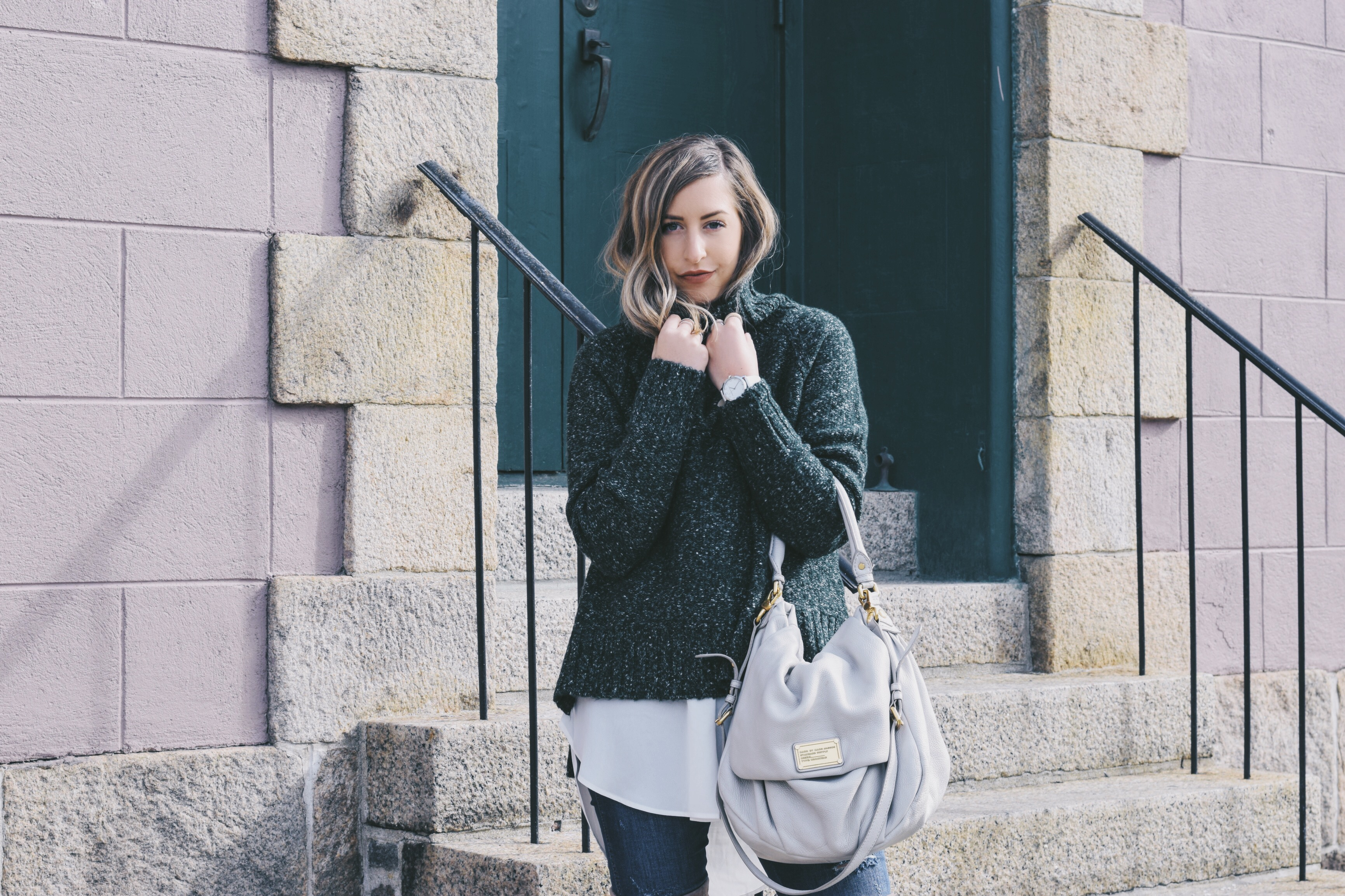 keeping warm in a green oversized knit sweater